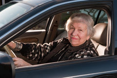 86 year old woman at her home, drivingn her car. 86 year old woman looking out driver's window Royalty Free Stock Photography