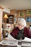 87 year old woman reading at home. 87 year old woman at home reading paper. USA stock image
