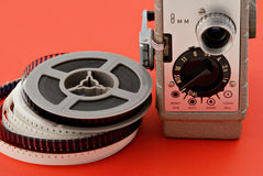 8mm Movie Camera & Reel. Old 8mm movie camera with film reels on a bright red background Stock Photography