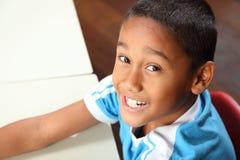 9个男孩教室服务台他的学校微笑的年& 图库摄影