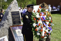 9 11 Ceremony Memorial Wreath Presenation. A police officer and sheriff's deputy lay a ceremonial wreath in front of a local 9/11 memorial at a ceremony on 9/11/ stock photo