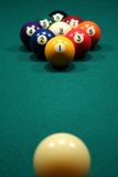 9-Ball rack of billiard balls. Focus is on the rack rather than the cue ball stock photography