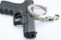 9 die automatische Millimeter-Pistole und die Polizei fesselt mit Handschellen Stockbild