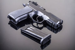 9 mm pistol. 9 mm hand gun on glass table with reflection Royalty Free Stock Images