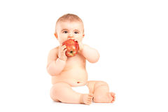 A 9 months old baby boy sitting and eating an apple Royalty Free Stock Images