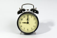 9 o'clock. Old fashioned alarm clock showing 9 o'clock on a white background stock images