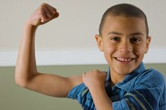 9 Year Old Boy Showing Off His Muscles. Cute 9 year old multi racial boy is proudly showing off his muscles while giving a winning smile Stock Photography