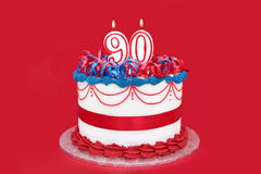90th Cake. With numeral candles, on vibrant red background Royalty Free Stock Photo