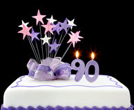 90th Cake. Fancy cake with number 90 candles.  Decorated with ribbon and star-shapes, in pastel tones on black background Royalty Free Stock Photography