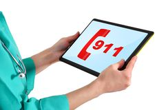 911 symbol on tablet. Doctor with 911 symbol on touchpad Royalty Free Stock Images
