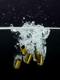 9mm cases with splashing water. On a black background Stock Photography