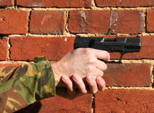 9mm Pistol. A 9mm Pistol being fired with  ejected case in the air this is against a brick wall Stock Photo