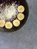 Açai-Rübe-Himbeerensmoothieschüssel mit Kokosnuss, Buchweizen, Bananenscheiben Stockbild