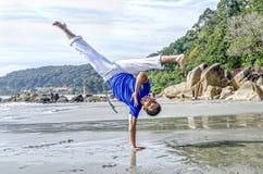 Ação acrobática do instrutor do capoeira na praia foto de stock