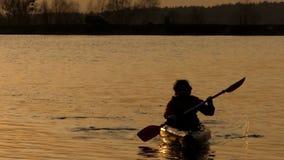 Ação bonita no por do sol, a vela do homem na canoa no lago video estoque