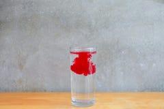 Ação da água da gota e do vidro de água na tabela de madeira na frente da parede do cimento Imagem de Stock Royalty Free