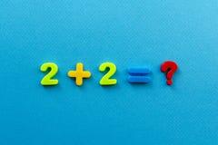 Ação da matemática dos números plásticos coloridos no fundo de papel azul foto de stock
