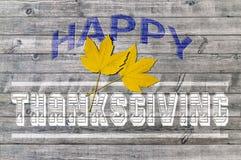 Ação de graças feliz azul e branca no fundo de madeira com a folha dois amarela Fotografia de Stock Royalty Free