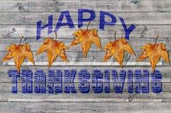 Ação de graças feliz azul no fundo de madeira com folha marrom Fotografia de Stock