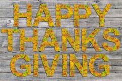 Ação de graças feliz escrita na placa de madeira com as palavras feitas das folhas Imagem de Stock