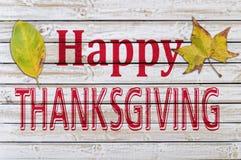 Ação de graças feliz escrita na tabela de madeira branca com outono dois Imagem de Stock