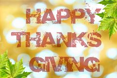 Ação de graças feliz escrita no fundo do bokeh com folha verde Imagem de Stock Royalty Free