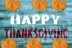 Ação de graças feliz escrita no fundo de madeira azul com folha Fotografia de Stock
