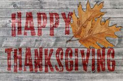 Ação de graças feliz vermelha escrita no fundo da placa de madeira com duas folhas Fotografia de Stock