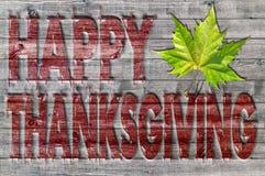 Ação de graças feliz vermelha escrita no fundo da placa de madeira com folha verde Imagens de Stock