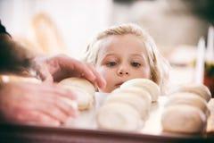 Ação de graças: Menina com fome que Eyeing Tray Of Rolls Fotografia de Stock