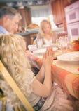 Ação de graças: A menina tem as mãos junto ao ter o jantar Imagens de Stock