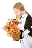 Ação de graças: Peregrino da menina que guarda a cesta de Autumn Leaves And F Imagem de Stock Royalty Free