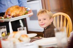 Ação de graças: Que sorri o menino esperas como Turquia é trazido apresentar Fotos de Stock Royalty Free
