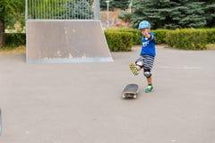 A ação disparou do menino novo que Skateboarding perto da rampa Foto de Stock