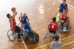 Ação do basquetebol da cadeira de rodas dos homens