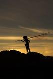 Ação do pescador no por do sol de pedra Fotografia de Stock Royalty Free