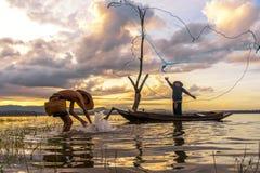 Ação do pescador quando rede de pesca no lago no pescador da manhã e da silhueta da luz do sol no barco, Fotografia de Stock