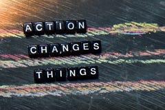 A ação muda as coisas - ATO em blocos de madeira Imagem processada transversal com fundo do quadro-negro imagens de stock