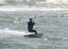 Ação recreacional dos esportes de água Um Kiteboarder que monta as ondas Dorset, Reino Unido Em maio de 2018 imagens de stock