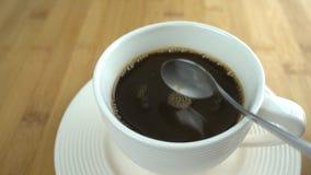 Açúcar branco de derramamento da colher na xícara de café video estoque