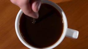 Açúcar da agitação da mão do ` s da pessoa no copo do café preto video estoque