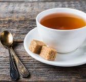 Açúcar de bastão marrom branco do copo e dos pires de chá em um fundo de madeira rústico Imagem de Stock