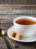 Açúcar de bastão marrom branco do copo e dos pires de chá em um fundo de madeira rústico Foto de Stock