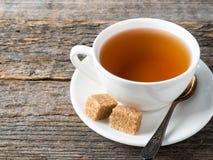 Açúcar de bastão marrom branco do copo e dos pires de chá em um fundo de madeira rústico Imagens de Stock Royalty Free