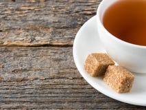 Açúcar de bastão marrom branco do copo e dos pires de chá em um fundo de madeira rústico Foto de Stock Royalty Free