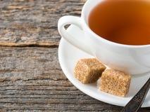 Açúcar de bastão marrom branco do copo e dos pires de chá em um fundo de madeira rústico Imagem de Stock Royalty Free