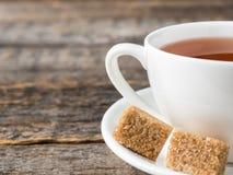 Açúcar de bastão marrom branco do copo e dos pires de chá em um fundo de madeira rústico Fotografia de Stock Royalty Free