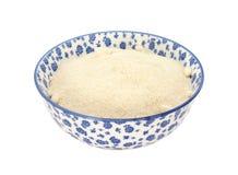 Açúcar de rodízio dourado em uma bacia azul e branca da porcelana foto de stock