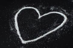 Açúcar derramado na forma do coração Imagens de Stock
