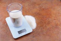 Açúcar em um copo de medição em escalas eletrônicas com um espaço da cópia foto de stock royalty free